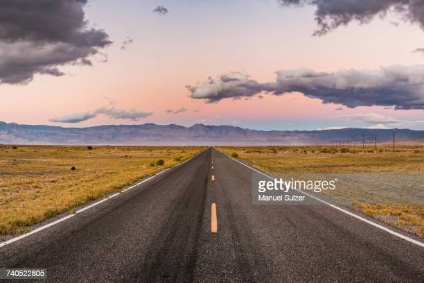 Straight road at sunset in Death Valley National Park, California, USA