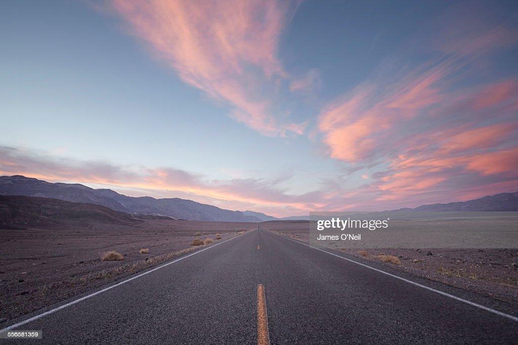 straight road in desert at sunset : Stockfoto