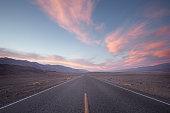 straight road in desert at sunset
