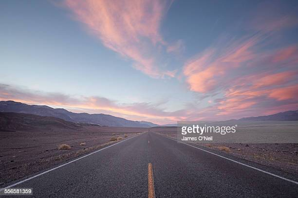 straight road in desert at sunset - avondschemering stockfoto's en -beelden