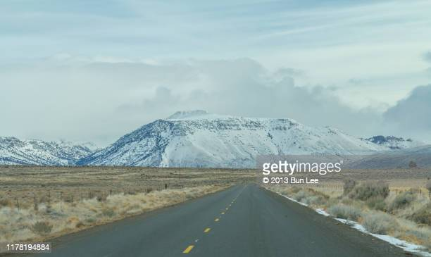 straight road into steens mountain - steens mountain stock pictures, royalty-free photos & images