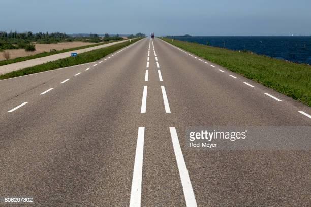 Straight road on dike between IJsselleer and nature reserve Oostvaardersplassen