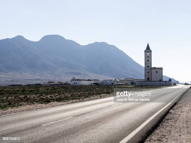 straight road that leads a small people close to the sea with a church and a great tower of belfry. beach the salt mines of cabo de gata and church the salt mines , natural park - nijar, almeria, andalucia, spain - moored stock pictures, royalty-free photos & images