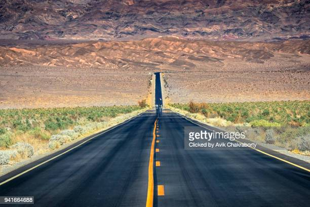 straight road through barren desert of death valley national park - sandy utah stock pictures, royalty-free photos & images