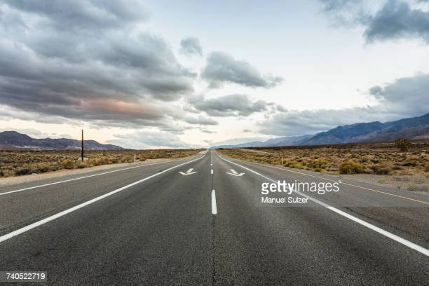 Straight road with direction arrows in Death Valley National Park, California, USA