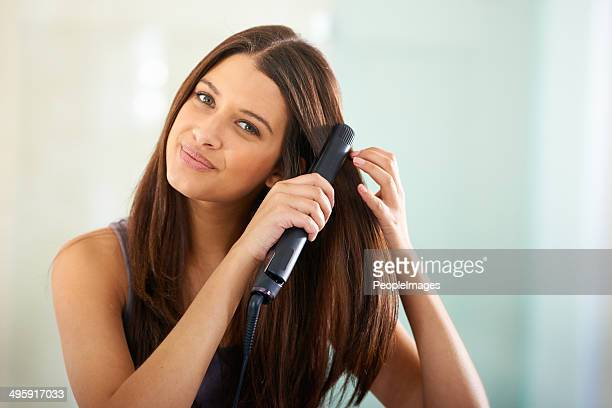 straightening her hair for that sexy look - straight hair stock pictures, royalty-free photos & images