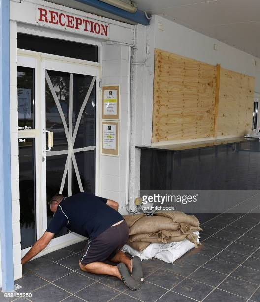 Strand Hotel manager John McBride is seen taping up the hotels doors and windows in preparation for Cyclone Debbie on March 27 2017 in Townsville...