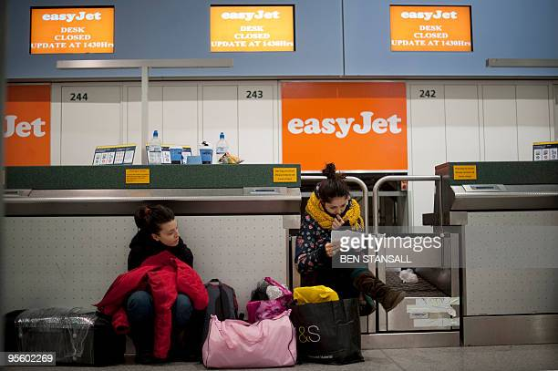 Stranded air passengers wait by an easyJet checkin desk after all easyJet fights were cancelled due to snow at Gatwick airport in Sussex southern...