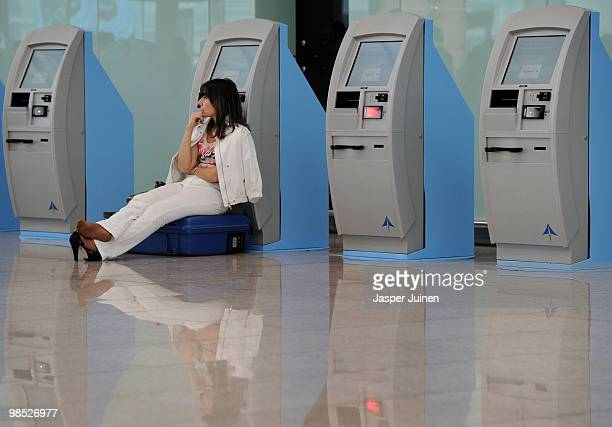 A stranded airline passengers waits seated on top of her suitcase and against a check in machine at El Prat international airport on April 18 2010 in...