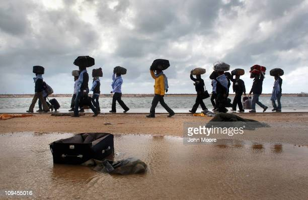 Stranded Bangladeshi workers walk along the beach at the port of Benghazi after failing to get on an evacuation ship on February 26 2011 in Benghazi...