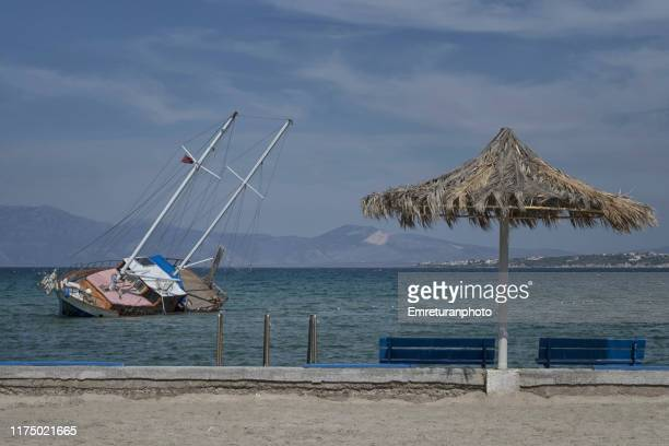 stranded boat along the beach with umbrella. - emreturanphoto stock pictures, royalty-free photos & images