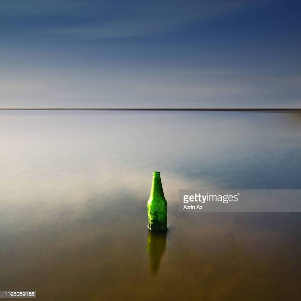 stranded bottle by the sea - azrin az stock pictures, royalty-free photos & images