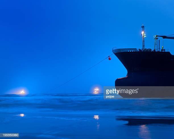 Gestrandete leer Frachtschiff am Strand und tugboats