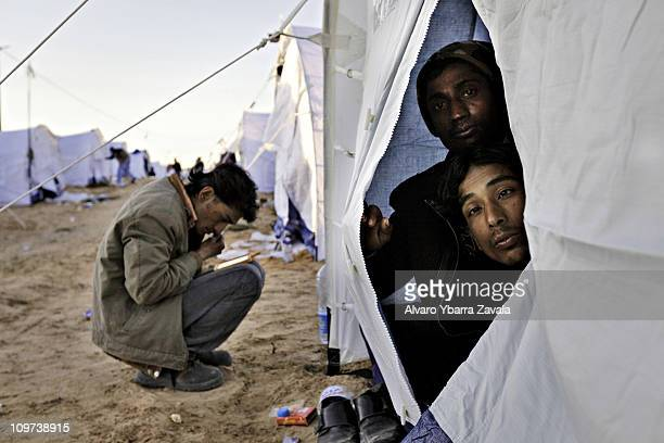 Stranded foreign workers from Bangladesh who have fled Libya at their tent in a camp on March 2 2011 in Ras Jdir close to the border between Tunisia...