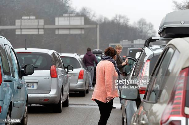 Stranded holidaymakers station on the A40 towards Geneva near Lyon central eastern France on February 21 as snow made access difficult towards the...