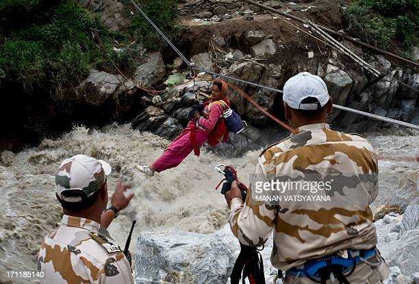 Stranded Indian pilgrim is transported across a river using a rope rescue system by Indo-Tibetan Border Police personnel in Govind Ghat on June 23,...