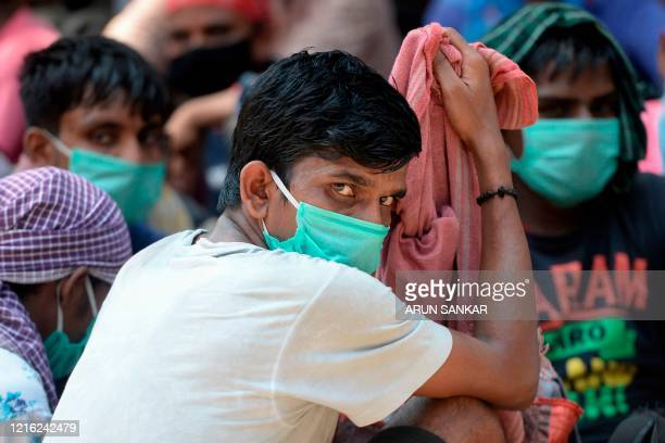 Stranded migrant labourers gather at an assembling centre to get transferred to a railway station to board on a special train to Bihar after the...