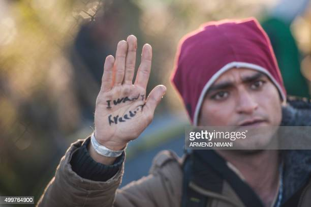 TOPSHOT A stranded migrant shows his hand bearing the slogan I want freedom as he and others try to cross the GreekMacedonian border near the village...