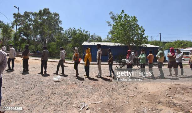 Stranded migrant workers and homeless people stand in a queue to collect food inside a government school on day nine of the 21day nationwide lockdown...