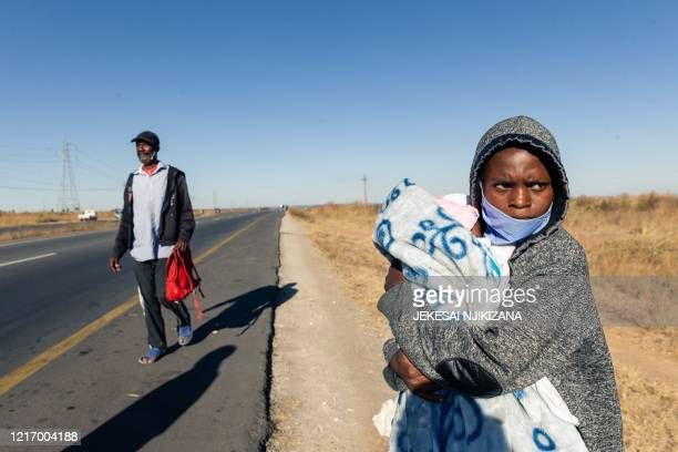 Stranded mother carries her child by a road with little traffic as she awaits transport to get into the central business district of Harare on June...