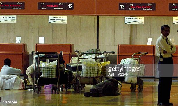 Stranded Pakistani passengers wait in front of the Pakistan International Airline boarding counters at Jinnah International Airport in Karachi 02...