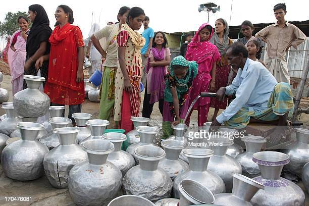 Stranded Pakistanis of Kurmitola Bihari Camp in Mirpur collect drinking water in a queue Dhaka Bangladesh August 05 2008