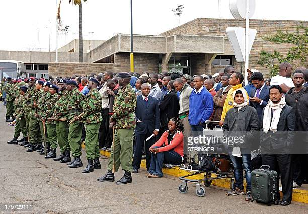 Stranded passengers and security personnel wait outside the Jomo Kenyatta International Airport in Nairobi on August 7 2013 A massive fire shut down...