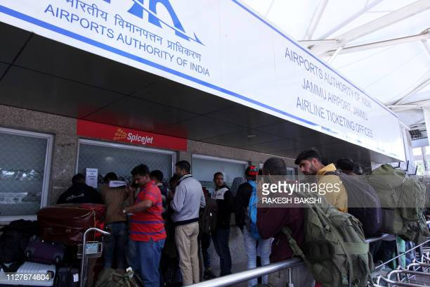 Stranded passengers queue at airline counters following the shut down of the airspace for commercials flights north of Delhi as tensions increase...