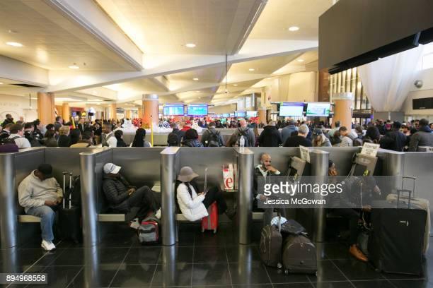 Stranded passengers relax near baggage claim at HartsfieldJackson Atlanta International Airport on December 18 2017 in Atlanta Georgia Hundreds of...