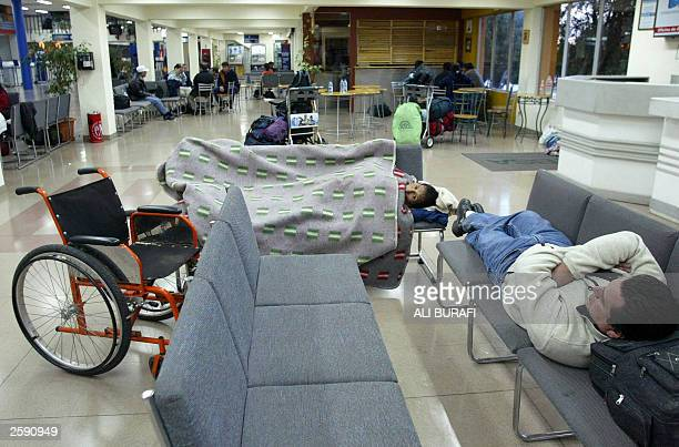 Stranded passengers rest while they wait for the reestablishment of the flights at El Alto airport in La Paz 13 October 2003 A soldier and 27...