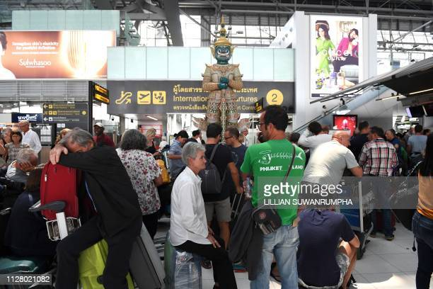 Stranded passengers wait at the check-in area at the Suvarnabhumi International Airport in Bangkok on February 28, 2019. - Thai airways cancelled 11...