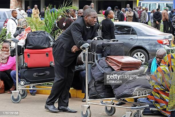 Stranded passengers wait outside the Jomo Kenyatta International Airport in Nairobi on August 7 2013 A massive fire shut down Nairobi's international...