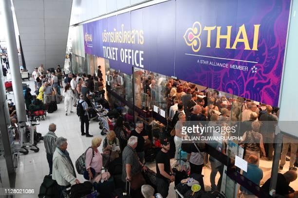Stranded passengers wait the Thai Airways ticket counter at the Suvarnabhumi International Airport in Bangkok on February 28, 2019. - Thai airways...