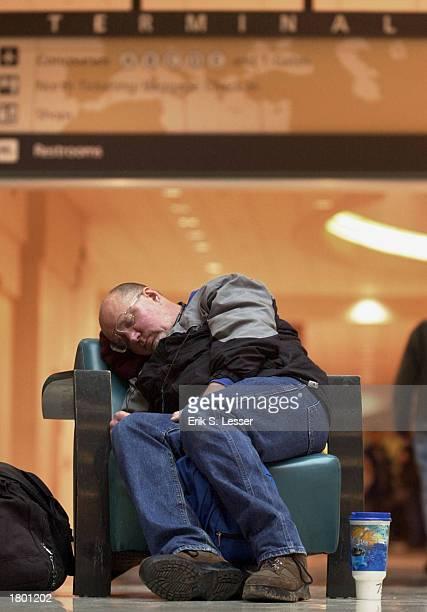A stranded traveler sleeps in the atrium area at Hartsfield Atlanta International Airport February 17 2003 in Atlanta Georgia The east coast snow...