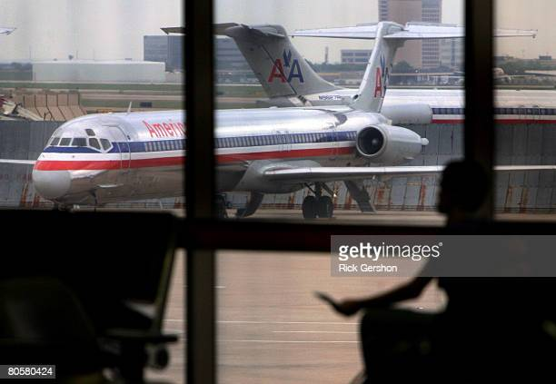 Stranded travelers wait in the terminal as grounded American Airlines MD80 aircraft sit on the tarmac April 9 2008 at the Dallas Fort Worth...