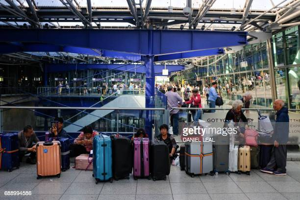 Stranded travellers sit with their luggage outside the departure area of Heathrow Airport Terminal 5 after British Airways flights were cancelled are...