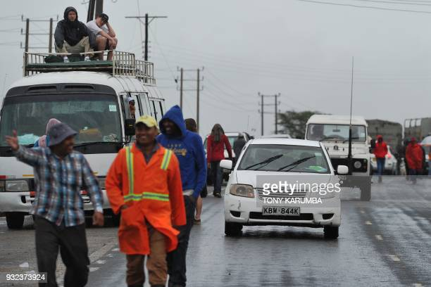 Stranded travellers wait out a flash flood that had engulfed a part of the main highway to Kenya's border town with Tanzania on March 15 2018 in...