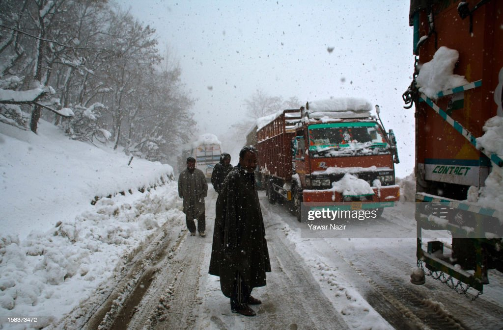 Stranded truck drivers wait on the highway next to their trucks amid heavy snowfall on December 14, 2012, in Banihal, 110 km (68 miles) south of Srinagar, the summer capital of Indian Administered Kashmir, India. Most parts of the Kashmir Valley, including Srinagar, received fresh snowfall, leading to closure of the 300 km (188 miles) Jammu-Srinagar Highway, the only road link between Kashmir and rest of India. Project Beacon authorities of the Border Roads Organisation, that maintains the highway, had already started efforts to clear the highway for traffic. The number of vehicles stranded on the highway was being ascertained.