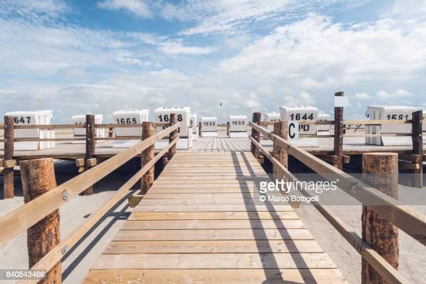 Strandkorbs on a wooder pier. St. Peter-Ording, Germany.