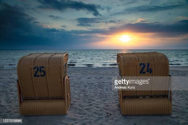 strandkörbe bei sonnenuntergang bei timmendorf strand auf insel poel in deutschland - insel stock pictures, royalty-free photos & images