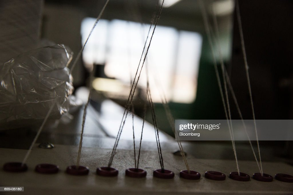 Strands of thread stretch from a knitting machine are seen at a Bodios Co. garment factory in Ulaanbaatar, Mongolia, on Wednesday, March 15, 2017. Mongolia's gross domestic product is expected to expand eight percent by 2019, and then grown at around five to six percent after that, International Monetary Fund (IMF) Mission Chief for Mongolia, Koshy Mathai, said in an interview last month with Bloomberg Mongolia TV. Photographer: Taylor Weidman/Bloomberg via Getty Images