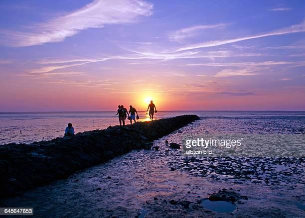 Strandwanderer auf einer Steinmole im Wattenmeer der Nordsee bei Niedrigwasser und untergehender Sonne