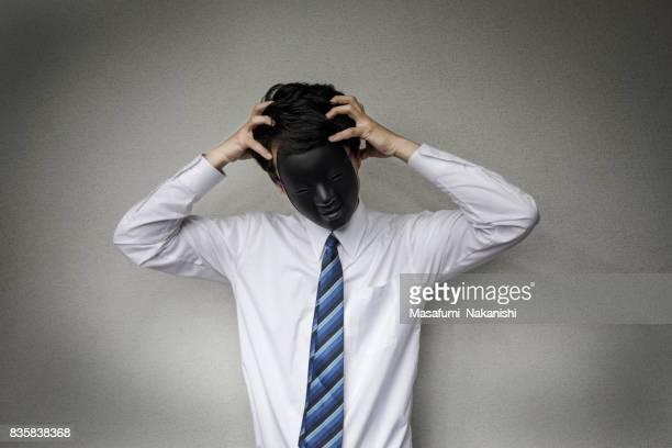 奇妙な仮面の実業家 - 手を顔にやる ストックフォトと画像