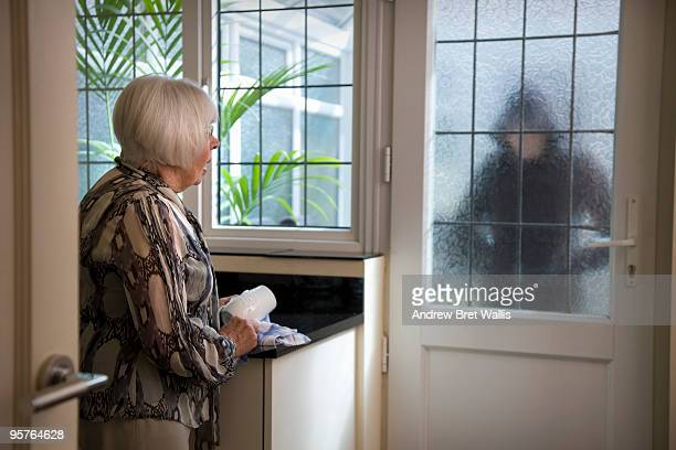 stranger at the door worrying an elderly woman - andrew dieb stock-fotos und bilder