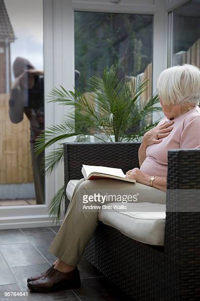 stranger at the window startles an elderly woman  - andrew dieb stock-fotos und bilder