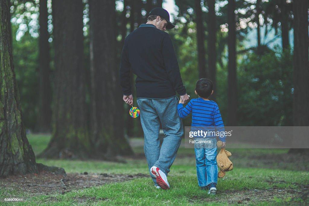 Stranger walking in a public park holding little boys hand : Stock Photo