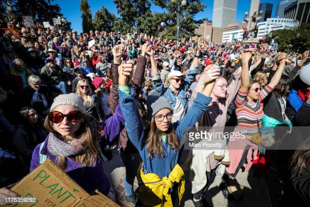 Strangers lock hands in solidarity while protesting climate change at the Fridays For Future Denver Climate Strike on October 11, 2019 at Civic...
