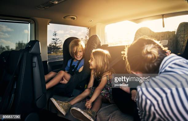 strapped in safely for his road trip - family inside car stock photos and pictures