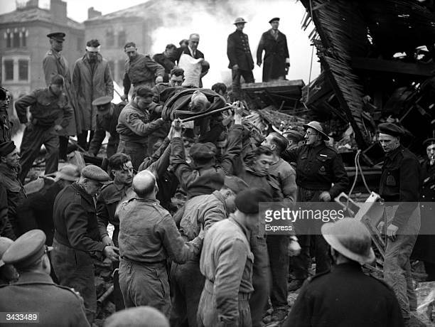 Strapped to a stretcher, a victim of a World War II bombing raid is carried from a pile of rubble in London.