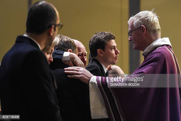 Strasbourg's archbishop JeanPierre Grallet comfort relatives during a funeral ceremony for French public national television broadcaster France...
